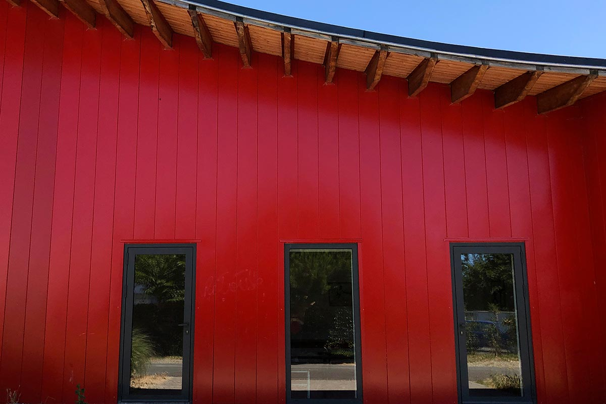 Front View Of The Bright Red Facade And The Wave-shaped Roof Of The Pierre De Coubertin Dojo Made At La Teste-de-Buch By Bulle Architectes.