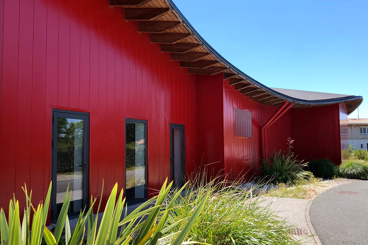 Red Facade With Wave-shaped Roof And Surrounding Vegetation Of The Dojo Pierre De Coubertin Realized At The Teste-de-Buch By The Agency Bulle Architectes.