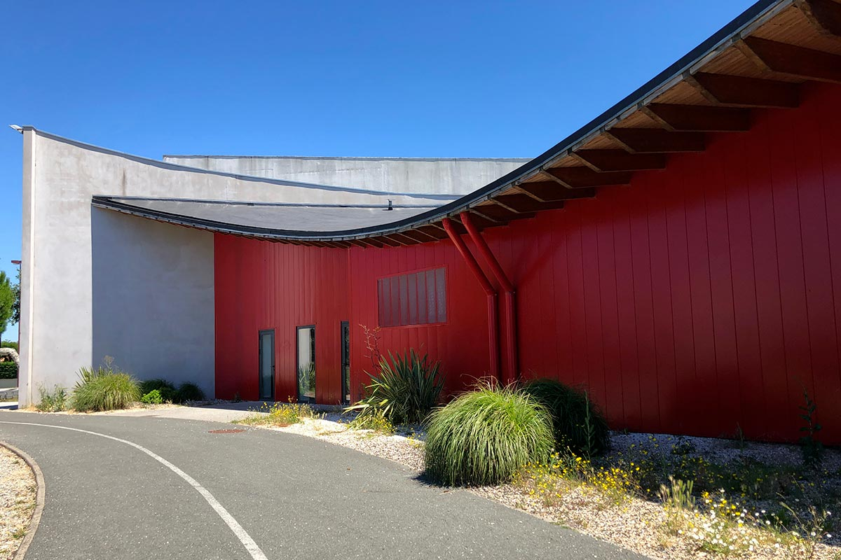 Red Facade With The Wave Roof Of The Dojo Pierre De Coubertin Realized At The Teste-de-Buch By The Agency Bulle Architectes.
