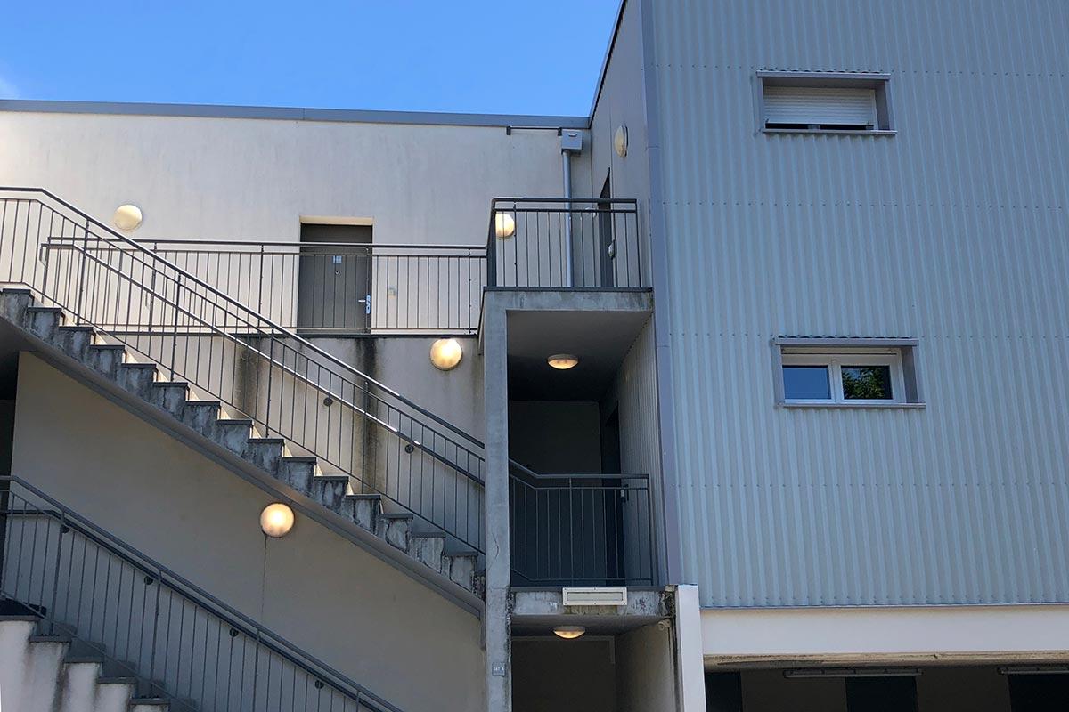 Vue Sur La Façade Intérieur En Tôle Ondulée Grise Côté Parking De La Résidence Tiscot Située à Blanquefort Et Réalisée Par L'agence Bulle Architectes.