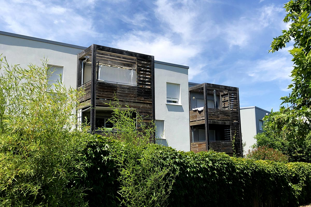View From The Street Behind A Vegetal Wall Of The Residence Tiscot With Its Wooden Balconies Which Is Located In Blanquefort And Realized By The Agency Bulle Architectes.