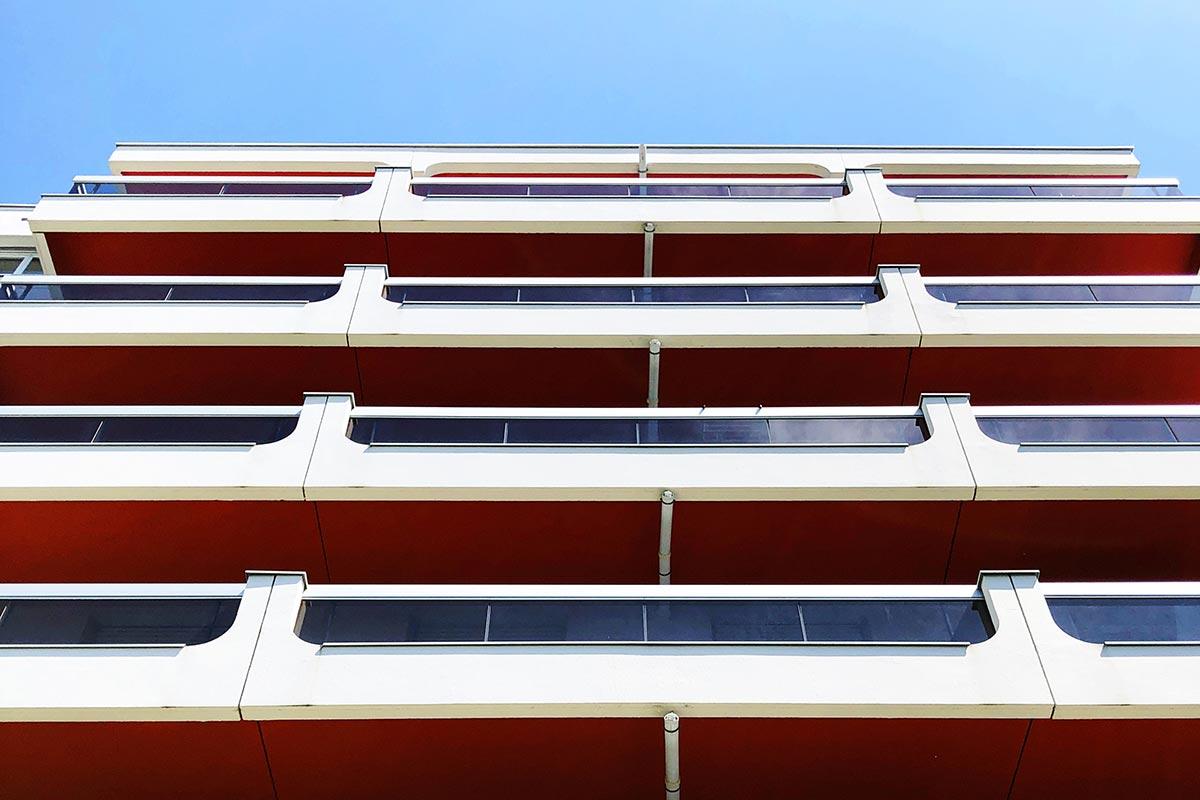 Vue De Face En Contre-plongée Des Balcons Aux Sous-faces Rouge De La Résidence Les Ecus Située à Eysines Et Réhabilitée Par L'agence Bulle Architectes.