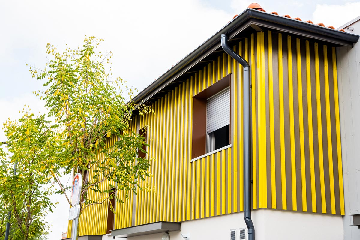 Zoom On A Yellow Wood Cladding Facade Of A House Of The Residence L'Orée Du Parc Realized At Teich By The Agency Bulle Architectes.