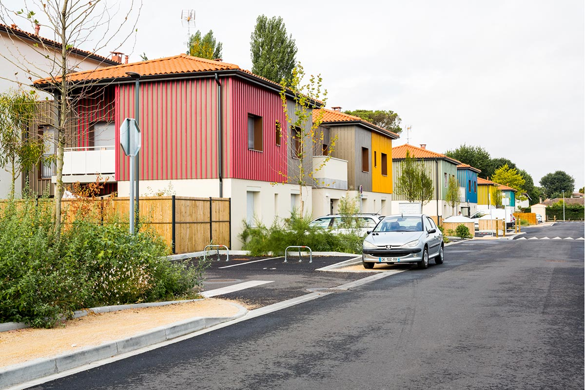 View From The Road Of The Buildings With Coloured Wood Siding Placed In The Row Of The Residence L'Orée Du Parc Realized At Teich By The Agency Bulle Architectes.