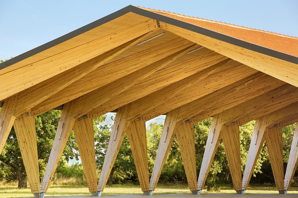 Vue De Biais De La Halle Couverte En Bois Du Teich Réalisée Par L'agence Bulle Architectes Avec Une Structure De Poteaux En V.