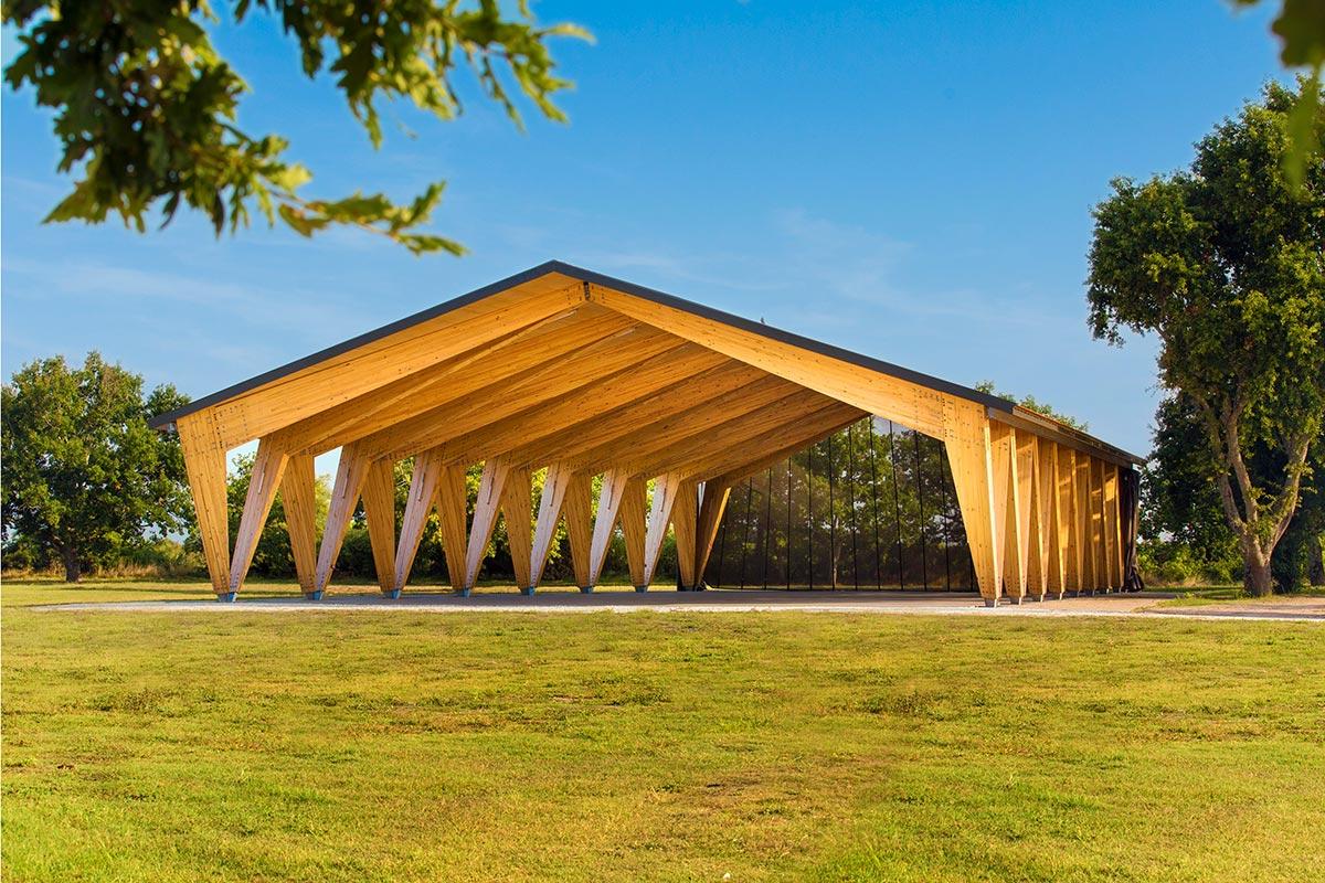 Vue éloigné Avec La Végétation Environnante De La Halle Couverte En Bois Du Teich Réalisée Par L'agence Bulle Architectes.