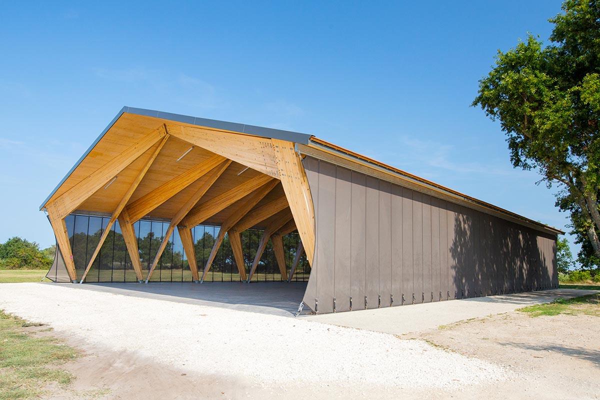 Vue Depuis L'extérieur De L'ensemble De La Halle Couverte En Bois Du Teich Réalisée Par L'agence Bulle Architectes.