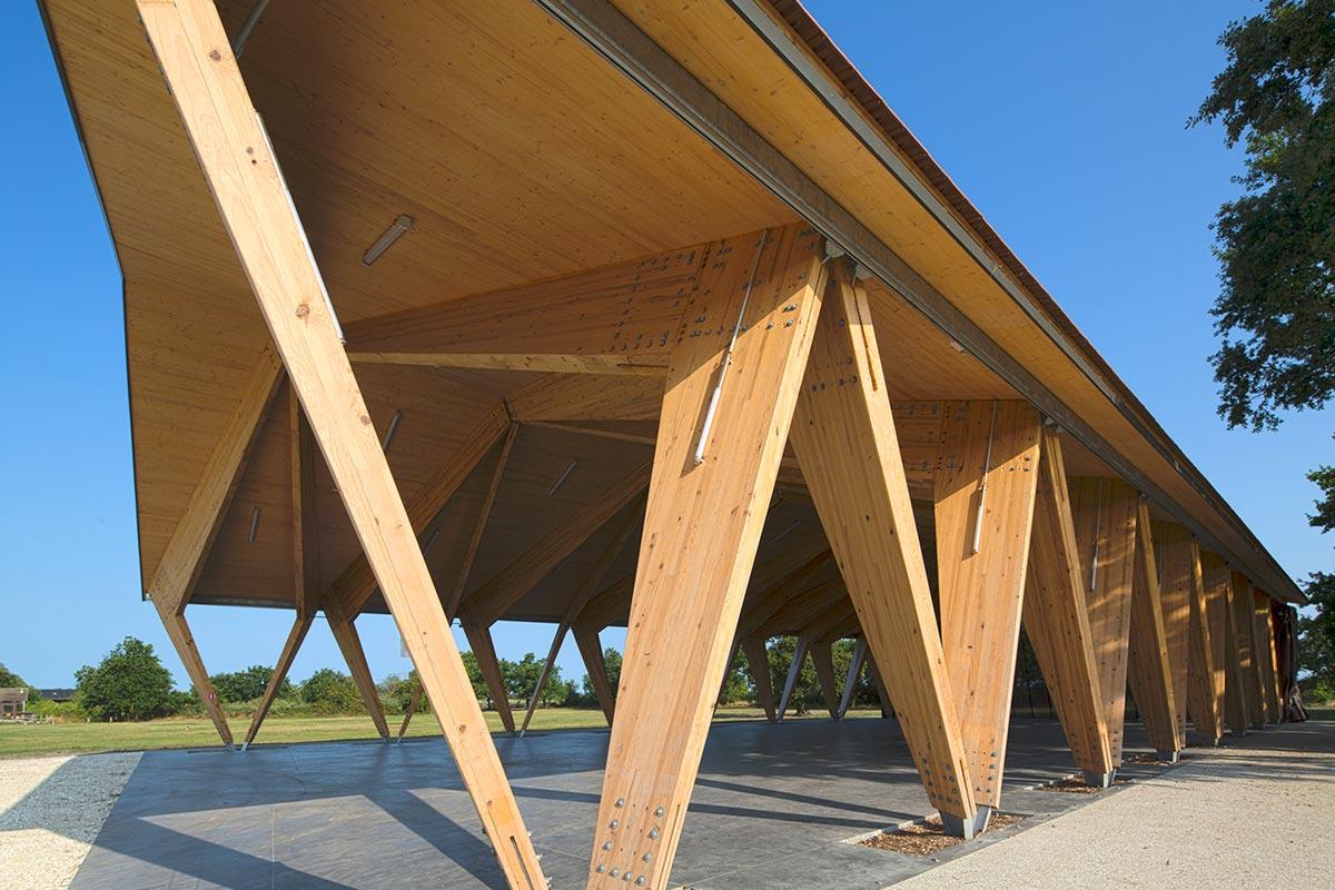 Vue En Contre-plongée Depuis L'extérieur De La Halle Couverte En Bois Du Teich Réalisée Par L'agence Bulle Architectes.