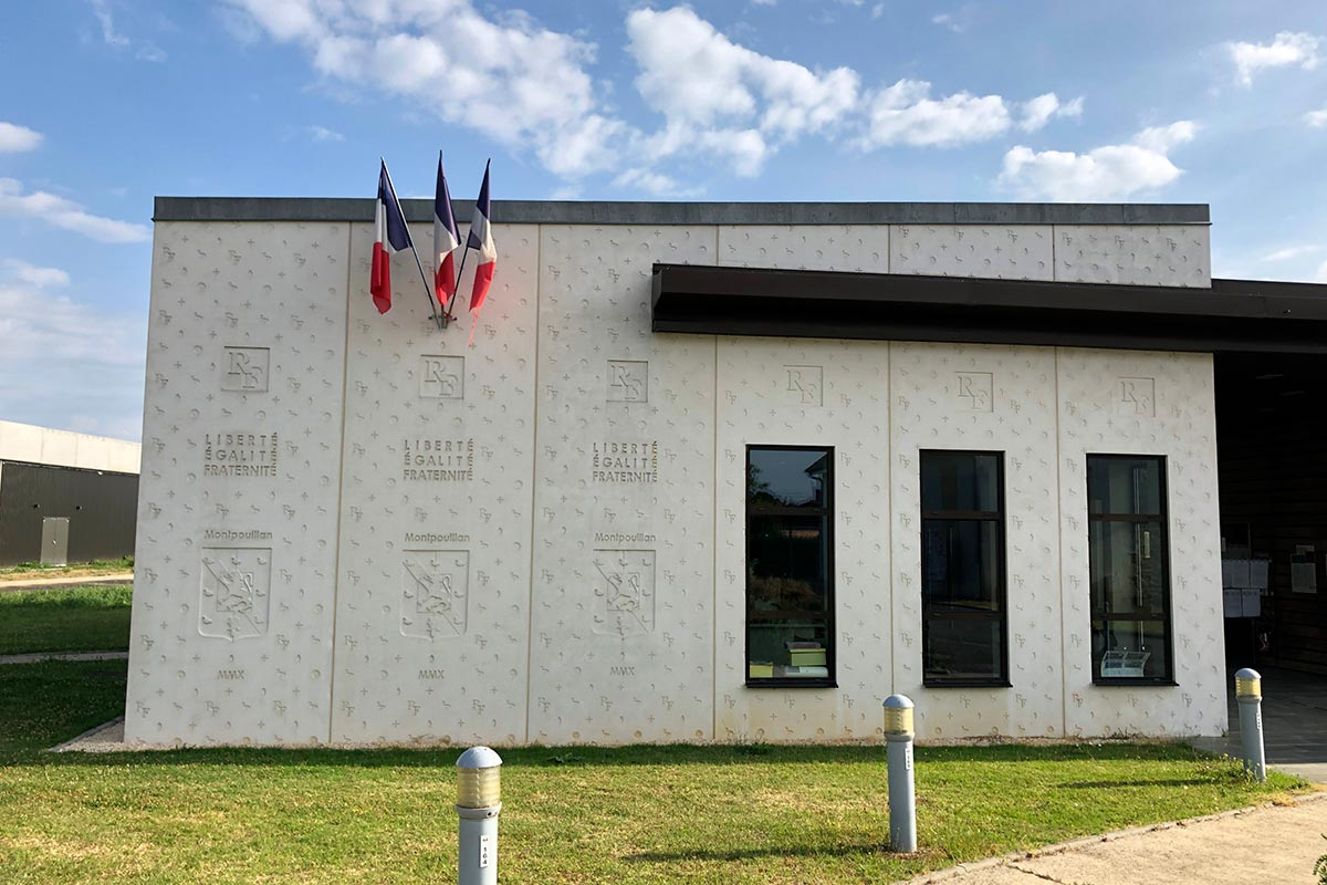 Left Side Of The Main Facade In Concrete Stamped With The French Flag Of The Town Hall Of Montpouillan Carried Out By The Agency Bulle Architectes.