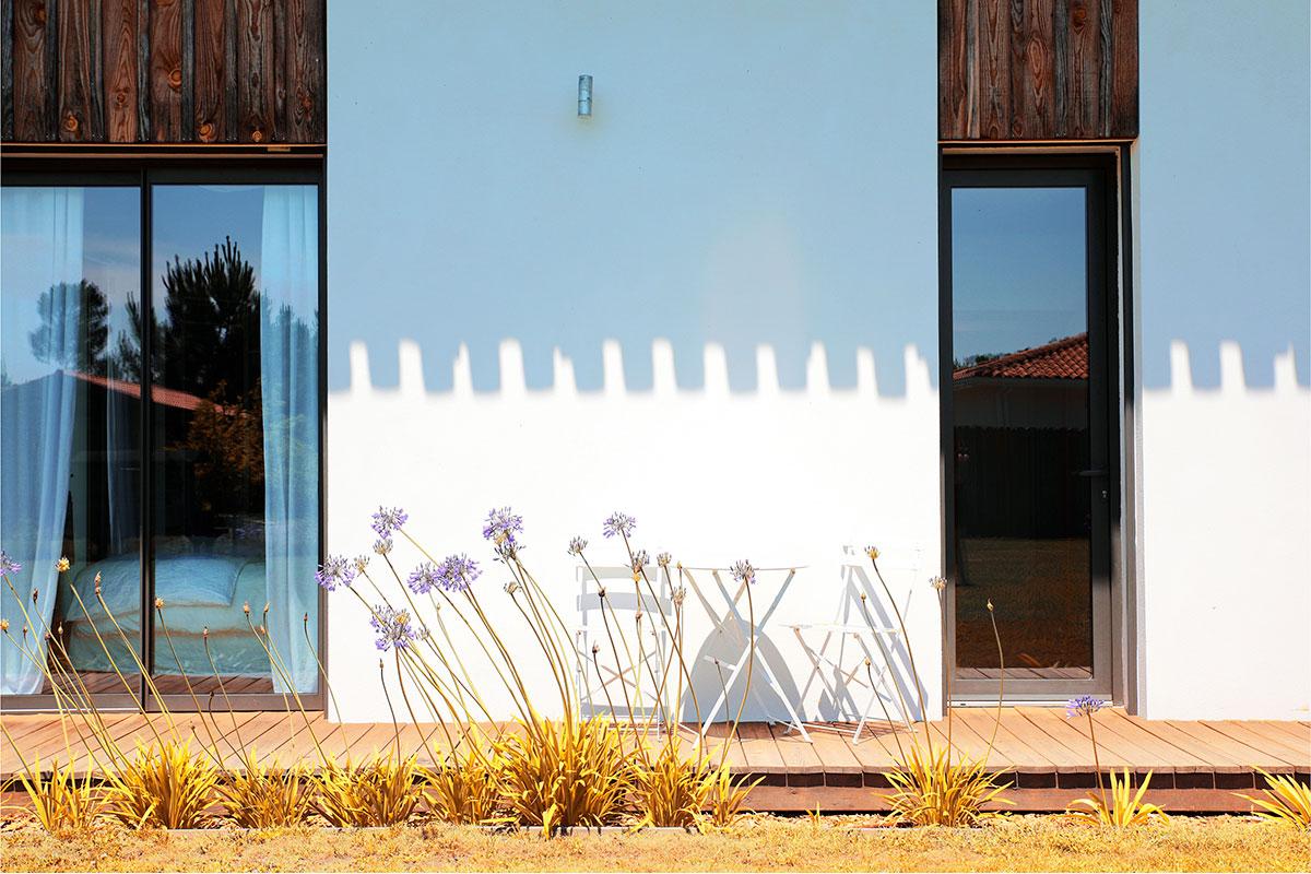 Vue De Face De La Façade Côté Terrasse Avec Des Fleurs Et L'ombre De La Toiture Projetée Sur La Façade.