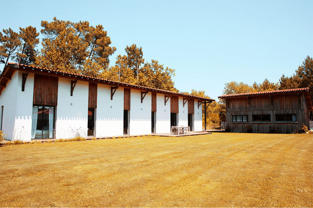 Vue Globale Extérieure De L'habitation Réalisée Par Bulle Architectes à Biscarrosse Ainsi Que De La Grange Située En Arrière-plan Perpendiculaire à La Maison Individuelle.