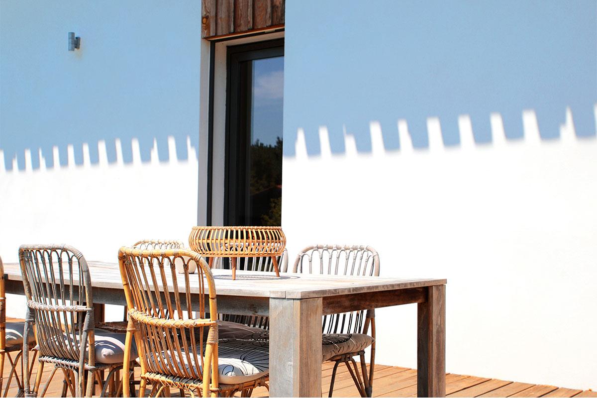 Zoom Sur Le Salon De Jardin Situé Sur La Terrasse D'une Maison Individuelle Réalisée Par Bulle Architectes à Bordeaux Avec Les Ombres De La Toiture Projetée Sur La Façade En Arrière-plan.