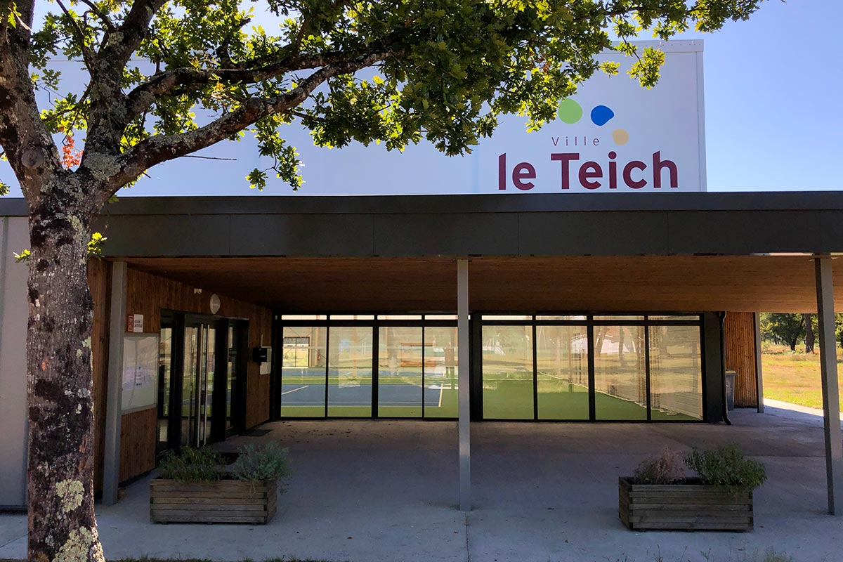 View Of The Main Entrance With The Logo Of The City Of Teich On The Facade Of The Tennis Club Of Teich Realized By The Agency Bulle Architectes.